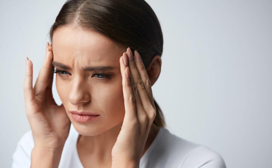 HODEPINE PÅ JOBB: Flere ting på jobben kan trigge hodepine: stress, ugustig sittestilling, lys og støy. Tøying, pauser og trening er alt ting som kan hjelpe, men det å gjøre forandringer på arbeidsplassen kan også være viktig. FOTO: NTB Scanpix