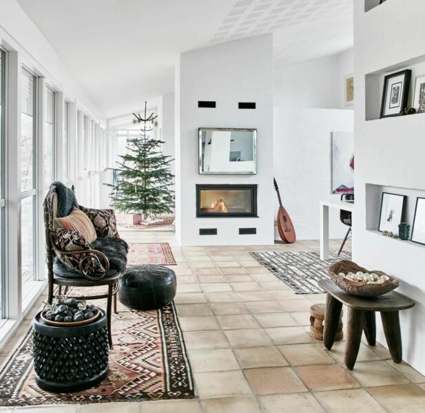 Fyr i peisen, kelimputer, tepper og arvestykker gir en varm kontrast til husets stramme arkitektur. Benken ved vinduene er et arvestykke, og stammer fra da Saras forfedre bodde i Afrika under kolonitiden. FOTO: Birgitta Wolfgang
