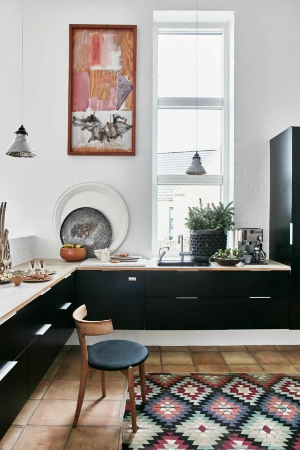 Marokkanske runde fat står på kjøkkenbenken sammen med en afrikansk trekurv fylt med gran. Den fine italienske trestolen er fra et loppemarked, mens de franske industrilampene er fra Suzanne Varming Antik. Det svarte kjøkkenet er fra Invita. FOTO: Birgitta Wolfgang