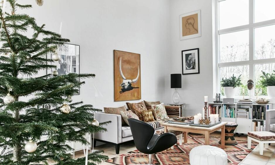 ET MODERNE JULEHJEM: Sara mikser sin eksotiske stil med nordisk enkelhet i stuen. Sofaen fra Eichholtz er kjøpt i Paris, sofabordet er produsert av Haslev Møbelsnedkeri, og bordlampen er fra Ochre. Maleriet har Sara selv malt, mens kelimteppet, puter og krakker er fra Brandts Indoor. Reolen er fra Montana. FOTO: Birgitta Wolfgang