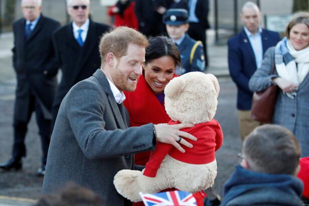 GAVE FRA FOLKET: Hertuginne Meghan og prins William tok seg god tid til å hilse på folket ved Hamilton Square i Birkenhead, og fikk blant annet en stor teddybjørn til sitt ufødte barn. FOTO: NTB Scanpix