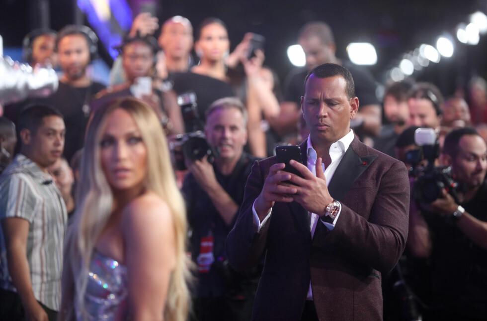 Jennifer Lopez sammmen med kjæresten Alex Rodriguez på rødløper. Rodriguez beundrer Lopez mens han tar bilder av henne. (Relationship goals!) Foto: NTB Scanpix