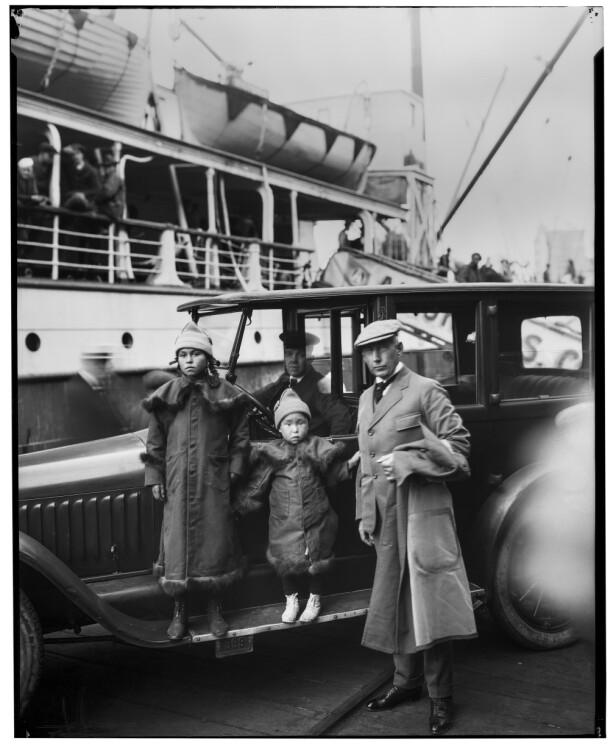 MASSIV OPPMERKSOMHET: Dette bildet er tatt på kaia i Seattle i 1921. Lille Nita i midten, omringet at «storesøster» Camilla og «Bettepappa» Roald Amudsen. Sjåføren i bakgrunnen. FOTO: Utlånt av Forlaget Press // Fra boken Kapp Hjertestein