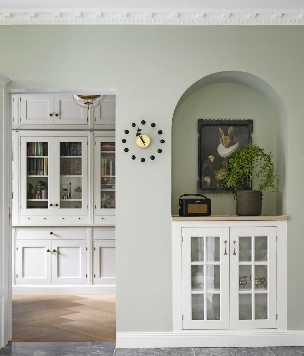 Du kan binde to rom sammen ved å bygge inn møbler i samme stil. Skapveggen er av elementer fra Kvänum, som også står bak kjøkkenet. Georg Nelson-uret er fra Paustian, serveringsbrettet på veggen er fra franske Ibride, og radioen er fra Roberts. FOTO: Frederikke Lea Heiberg
