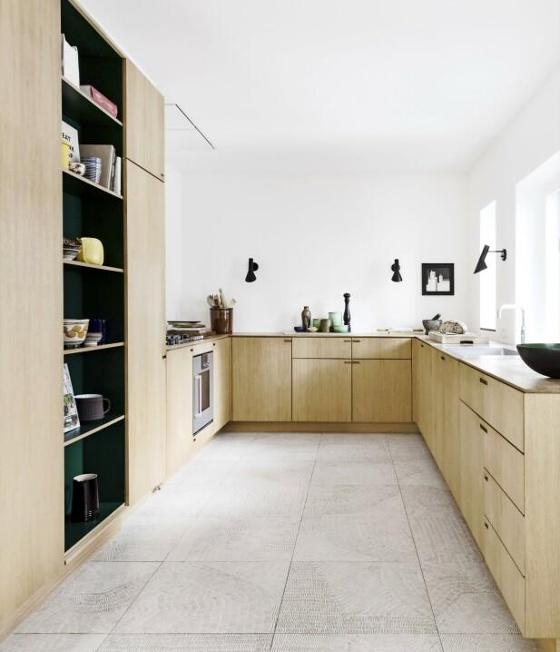 Velg et kjøkken med materialer og stil som passer til huset og den tiden det ble bygget. Kjøkkenet i massivt eiketre er fra Nicolaj Bo. De svarte AJ-vegglampene, designet av Arne Jacobsen, er fra Louis Poulsen. De italienske flisene med tegnede fossiler fås hos Banio. FOTO: Anitta Behrendt