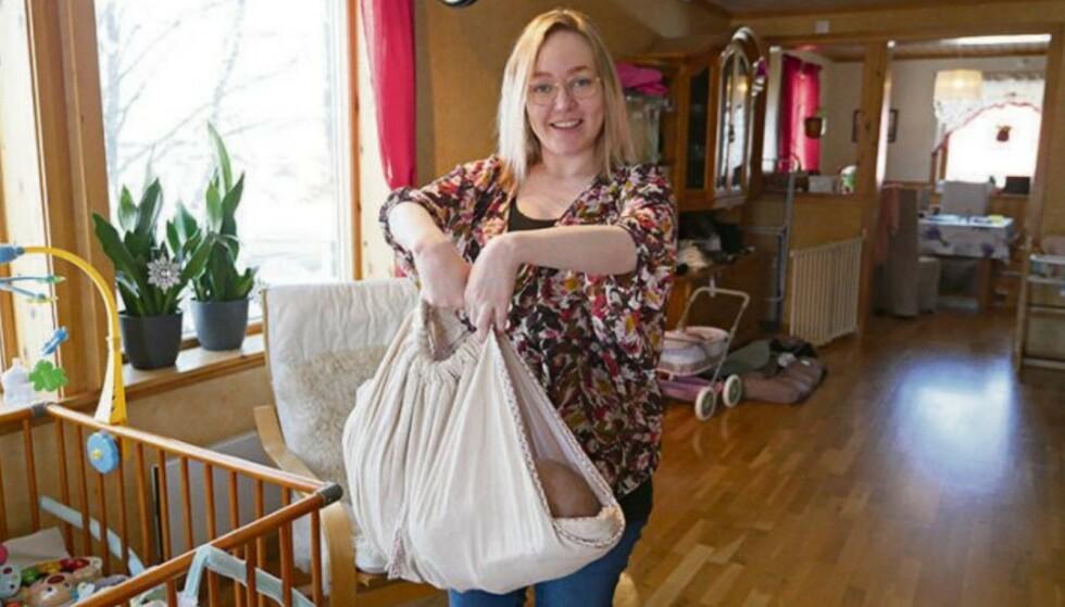 BABY HAMMOCK: - Mange hjelpemidler som blir dømt nedenom og hjem av funksjonsfriske mødre, kan være til god hjelp for meg, sier Lena Iren. Her demonstrerer hun baby hammocken hun bruker for å løfte babyen. FOTO: Privat