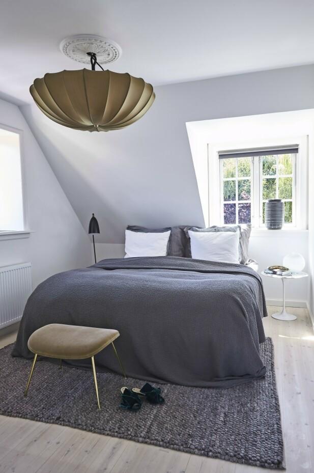 Soverommet er innredet med sengeteppe fra Rue Verte, gulvteppe fra Hay og taklampe fra Christine Calleen. Sengetøyet kommer fra Semibasic og sidebordet i marmor fra Knoll. FOTO: Ditte Capion