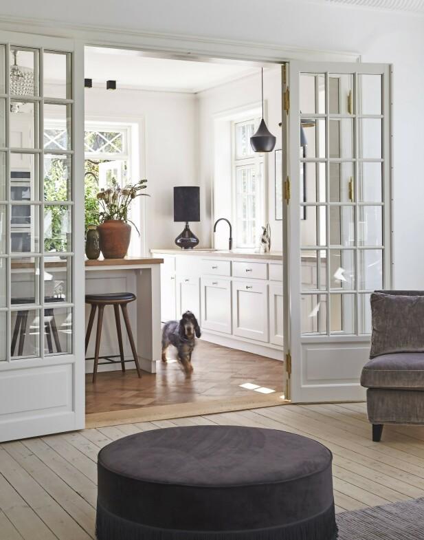 Kjøkkenet er åpent, mot både stuen og spisestuen, og familien kaller det husets hjerte. Og sjekk så søt hunden Helge er! FOTO: Ditte Capion