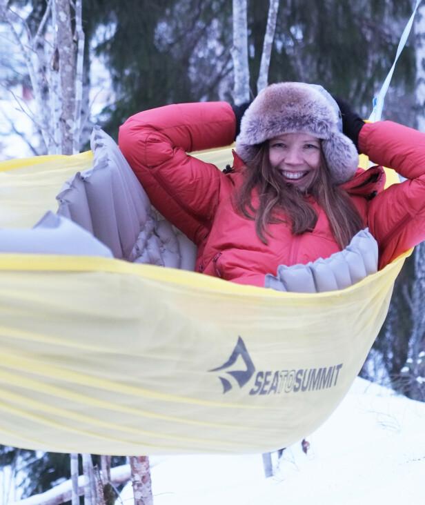 PÅ VINTERSTID: Det er ikke noe problem å campe ute i hengekøye om vinteren, slik som Hege gjør her, så lenge man husker varme klær, en god sovepose for vinterstid - og ikke minst et solid liggeunderlag. FOTO: Schultz Heireng