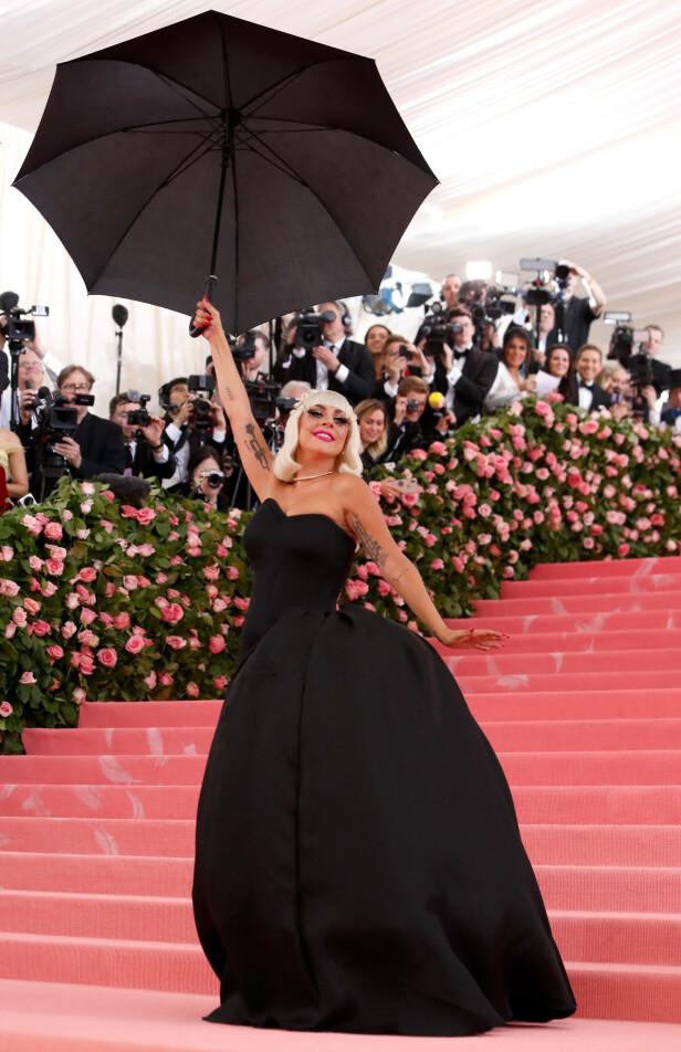 ENKLERE LOOK: Hennes andre antrekk var en svart kjole med matchende paraply. Foto: Scanpix