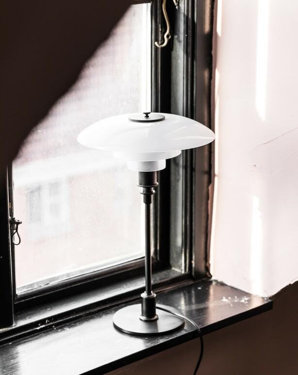 De svartmalte vinduskarmene er en av mange detaljer i leiligheten. Her står en designlampe signert PH.
