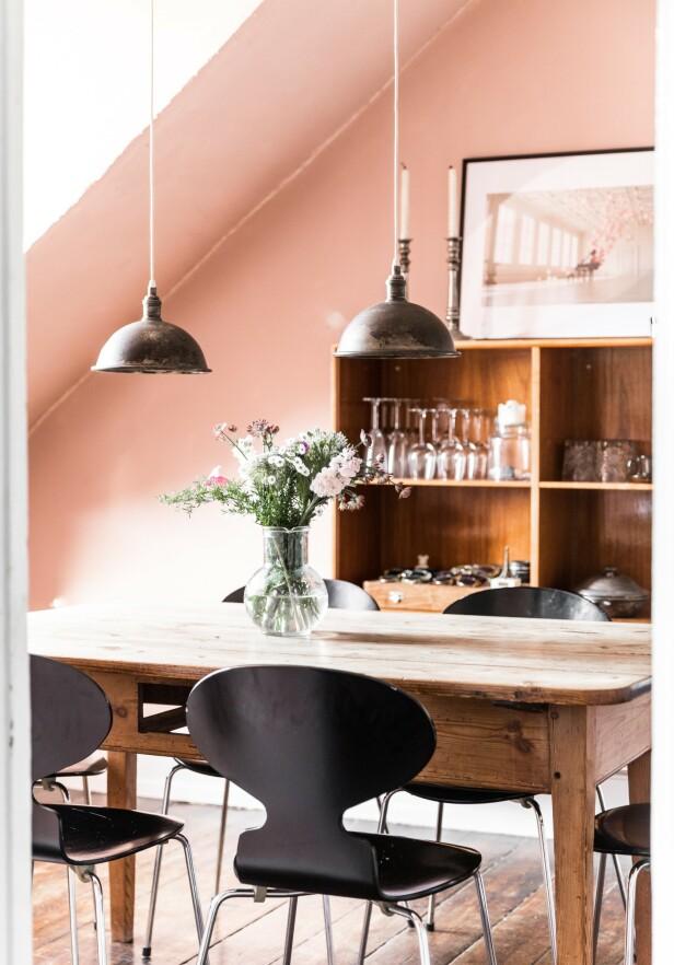 Kombinasjonen av de klassiske, stramme Arne Jacobsen-stolene og det grove spisebordet skaper god stemning i spisestuen.