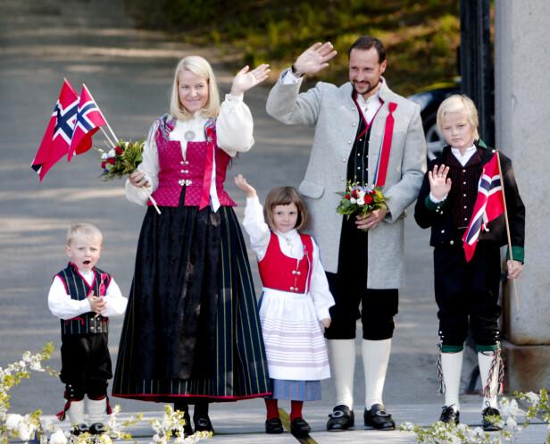 STASELIG: Stadig flere menn velger å gå i bunad, og kronprins Haakon er blant dem. Dette bildet er tatt på Skaugum i 2008, da kronprinsfamilien vinket til barnetoget. Haakon, Mette-Marit, prinsesse Ingrid Alexandra og prins Sverre Magnus var alle ikledd Askerbunaden, mens Marius Borg Høiby hadde på seg bunad fra Vest-Agder - der kronprinsessens familie har røtter. FOTO: NTB Scanpix