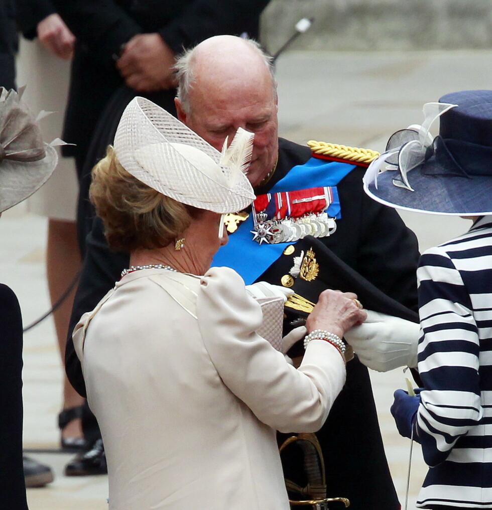 EN HJELPENDE HÅND: I likhet med bunadsbruk, kreves det også litt ekstra hjelp når man går med uniform. Her gir dronning Sonja ektemannen en hjelpende hånd utenfor Westminster Abbey i London i forbindelse med bryllupet mellom prins William og hertuginne Kate i 2011. FOTO: NTB Scanpix
