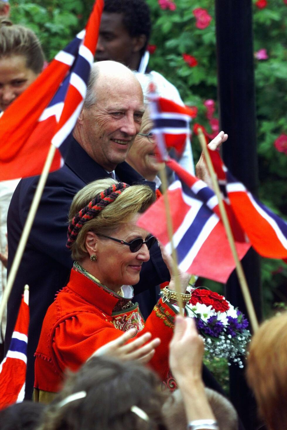 RØDTRØYEBUNAD: I 2000 var kongeparet til stede i Skien, for å ta del i feiringen av byens tusenårs jubileum - og dronningen var selvfølgelig ikledd Telemarksbunaden hun har fått av sin mor. Kongen var ikledd dress. FOTO: NTB Scanpix