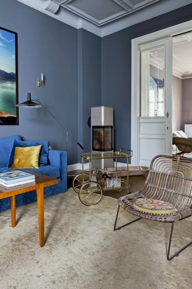 Den blå sofaen er fra Cramer Möbel + Design, og lampen er fra Baltensweiler. Sofabordet er vintage fra 60-tallet, og bambusstolen er fra Flamant. Lignende bartralle som den du ser på bildet, kan du finne hos Nordal. FOTO: Anne-Catherine Scoffoni