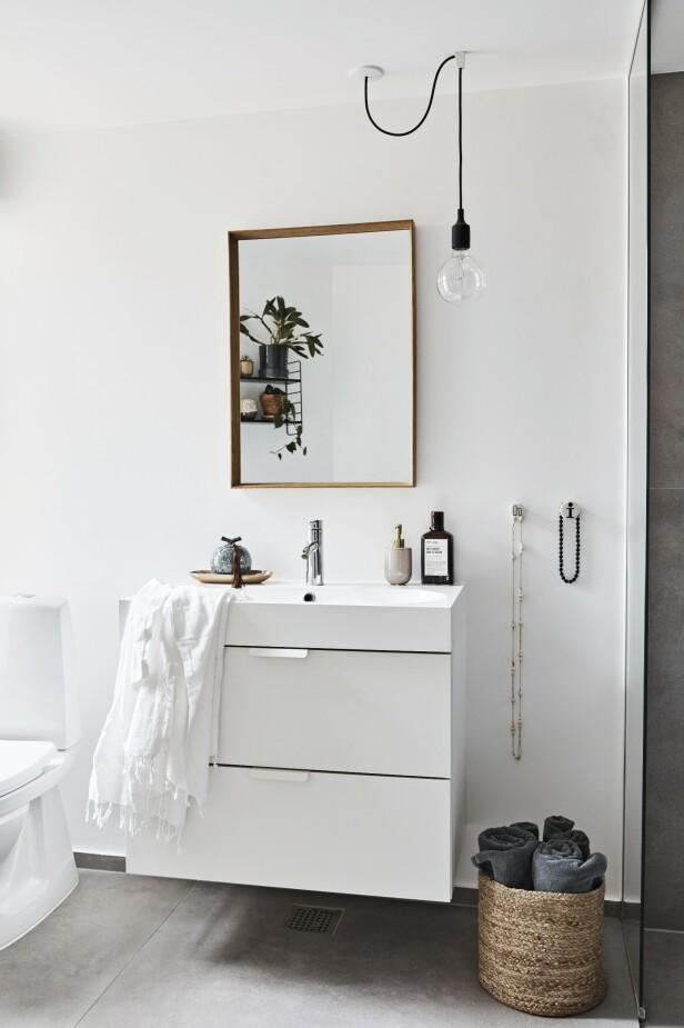 Stram baderomsinnredning og rene flater blir balansert med flettede kruver, linhåndklær og grønne planter. Lampen som henger fra taket, er fra Muuto, speilet fra Bolia og knaggene fra Liebe. FOTO: Dianna Nilsson