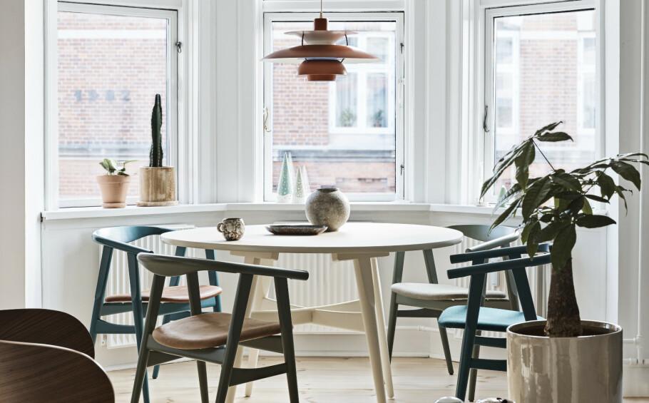 Spisebord og stoler er designet av Hans J. Wegner. Over spisebordet henger en PH-lampe som Lasse har arvet av farmoren sin. Skålen på bordet fant de på en reise til Vietnam. Tips! Lyst tre er perfekt for den skandinaviske stilen. FOTO: Dianna Nilsson