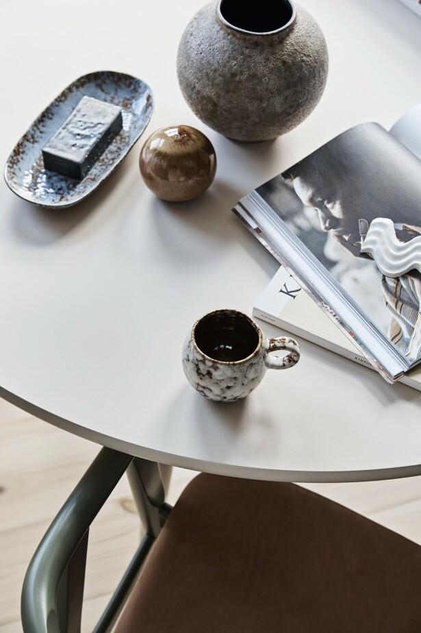 Hint av grønt dukker opp overalt i leiligheten, her på Wegner-stolen med grønne armlener og bein i kombinasjon med brunt skinntrekk. Keramikken på bordet har Stine laget selv. Tips! Tre, keramikk, skinn og stein er sanselige materialer som gir et naturlig preg. FOTO: Dianna Nilsson