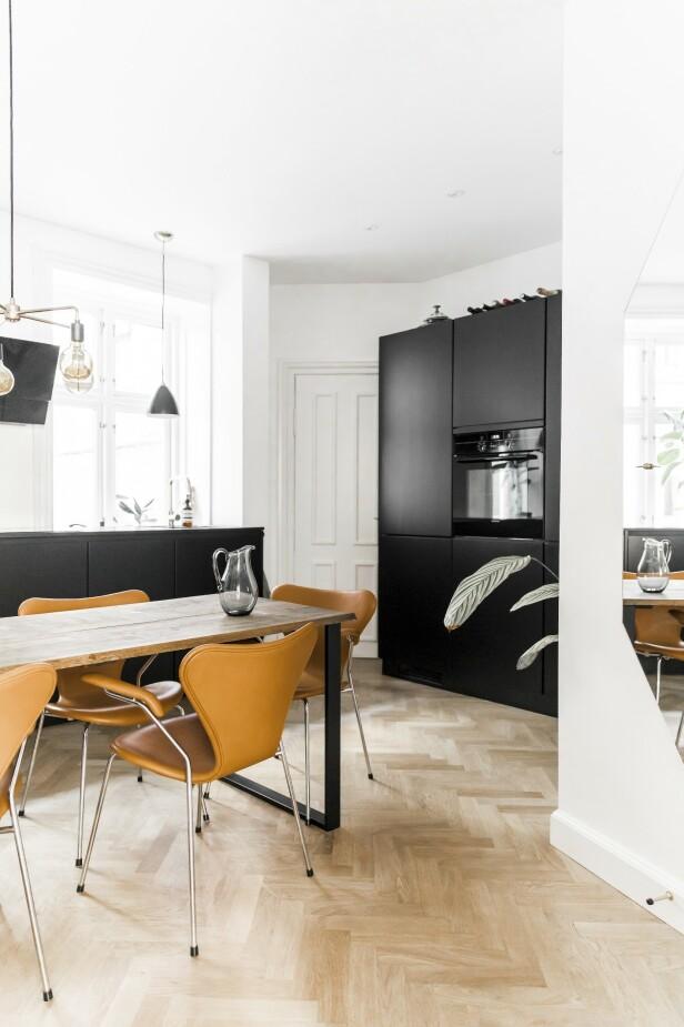 Fiskebeinsparketten ble valgt for å tilføre leiligheten et klassisk preg. Med et svart kjøkken får rommet en moderne kontrast.    FOTO: Julie Wittrup og Mikkel Dahlstrøm/Another Studio