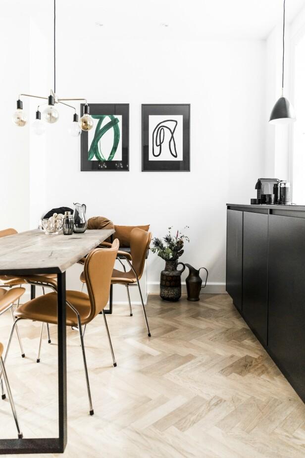 Kiki vurderte et kjøkken i eik, men var redd for at det ville bli for mye med tre på både gulv og fronter. Derfor endte hun opp med et stramt kjøkken fra Kvik. Spisebordet er spesiallaget, stolene er designet av Arne Jacobsen, og taklampen er fra Menu. Kunsten på veggen er hennes egen.  FOTO: Julie Wittrup og Mikkel Dahlstrøm/Another Studio