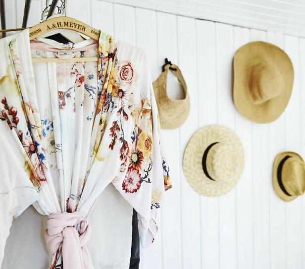 Stråhatter og en blomstrete kimono pynter opp den hvite veggen og skaper sommerstemning på soverommet. FOTO: Stylesystemet