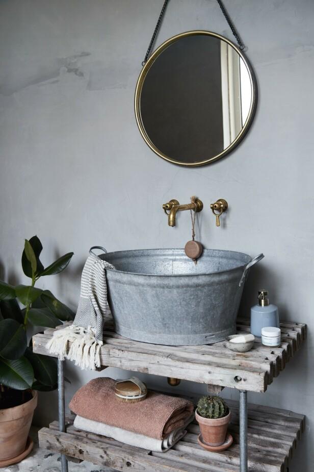Gullfarget, rundt speil fra Ilva og matchende armatur fra Toni gir en fin kontrast til resten av badet. Såpedispenseren og de to håndklærne på nederste hylle er fra Södahl. Tips! Runde speil er hot om dagen, og gjør mye for et rom. FOTO: Stine Christiansen