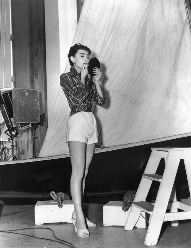 Stilikonet Audrey Hepburn kombinerer den rutete skjorten med en kort denimshorts og høye hæler. FOTO: Scanpix