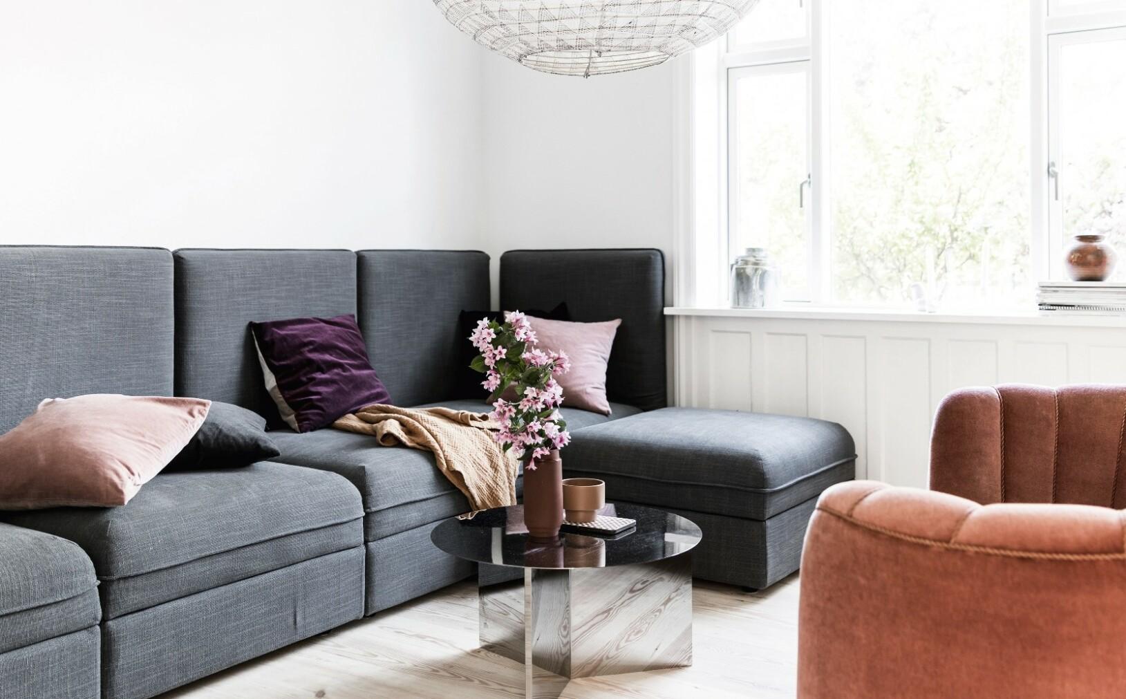 En praktisk, stram modulsofa fra Ikea står sammen med Ann-Sofies yndingsmøbel, nemlig den gamle velursofaen med myke former. Den store lampen fra Paris au Mois d'août får nesten bordet fra Hay til å til å se ut som en miniatyr. Tips! Spill på kontraster! I både form og størrelse. FOTO: Another Studio