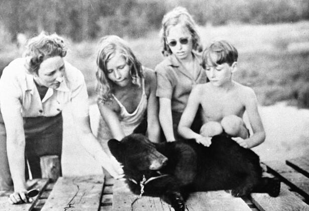 I LANDSFLYKTIGHET: Kronprinsesse Märtha med barna prinsesse Astrid, prinsesse Ragnhild og prins Harald under et besøk i den norske treningsleiren Little Norway, for norske flygere i Canada. Her klapper de bjørnen som var maskot i leiren. FOTO: NTB Scanpix