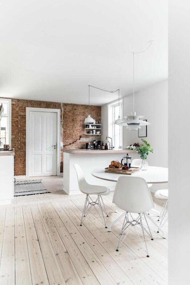 Det hvite kjøkkenet får litt «edge» og personlighet fra den rå mursteinsveggen og det originale tregulvet. FOTO: Julie Witterup og Mikkel Dahlstrøm/Another Studio