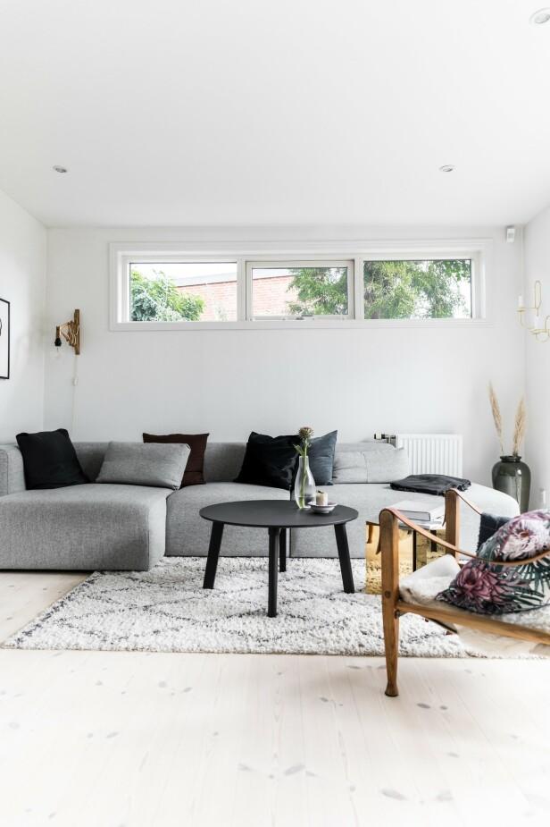 Det som før var en utestue har fått ny funksjon. Paret har valgt å isolere rommet, og bruker det nå som tv-stue. Sofaen og sofabordet er fra Hay. Teppet er fra Ellos, og bildene på veggen er fra Stilleben og Deseino. Vegglampen er fra loppemarked. FOTO: Julie Witterup og Mikkel Dahlstrøm/Another Studio