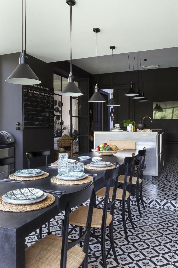 De kalde elementene i stål og betong på kjøkkenet balanseres av treverk og dekorative gulvfliser. FOTO: Anne-Catherine Scoffoni