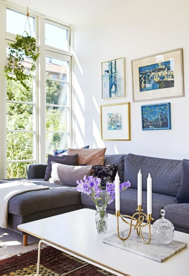Noe av kunsten på veggene har de arvet, noe har Christina laget, og noe er malt av en venn. Sofaen er fra Bolia og putene fra H&M Home, Hay, Notre Dame og Ikea. Bordet er fra Hay og lysestaken fra Skultuna. Glasskrukken og glassvasen er arvet. FOTO: Ditte Capion
