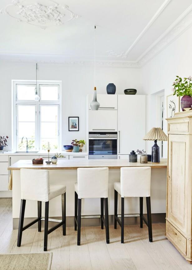 Barstolene er fra Ikea, og det gamle skapet er arvegods. Tips! Barstoler gjør det enkelt å holde hverandre med selskap mens maten lages. FOTO: Ditte Capion