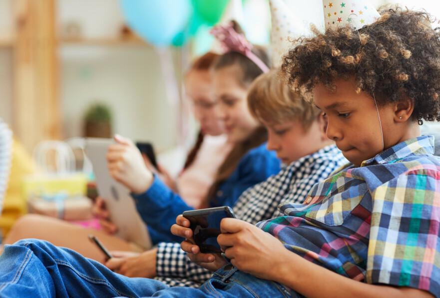 HEKTA PÅ MOBILEN: Kan barns mobilbruk gå ut over deres sosiale trening? FOTO: NTB Scanpix