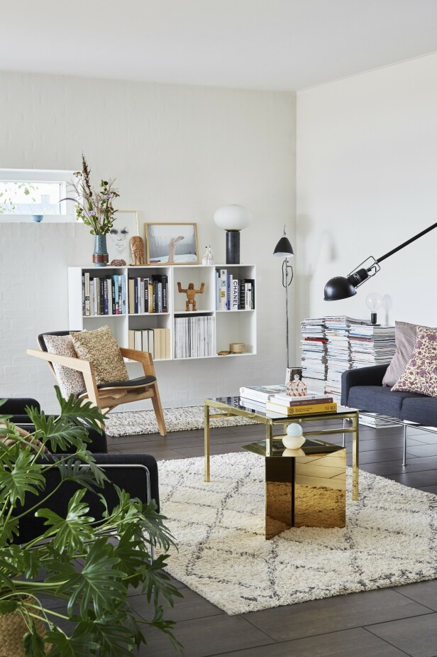 I stuen står sofa og stol fra Arne Jacobsen. De små blomstrete putene er hjemmesydde. Bordet med messingbein og glassplate er vintage, mens det lave gullbordet er fra Hay. Tips! Miks grove ullkvaliteter med blank messing for en effektfull kontrast. FOTO: Anitta Behrendt