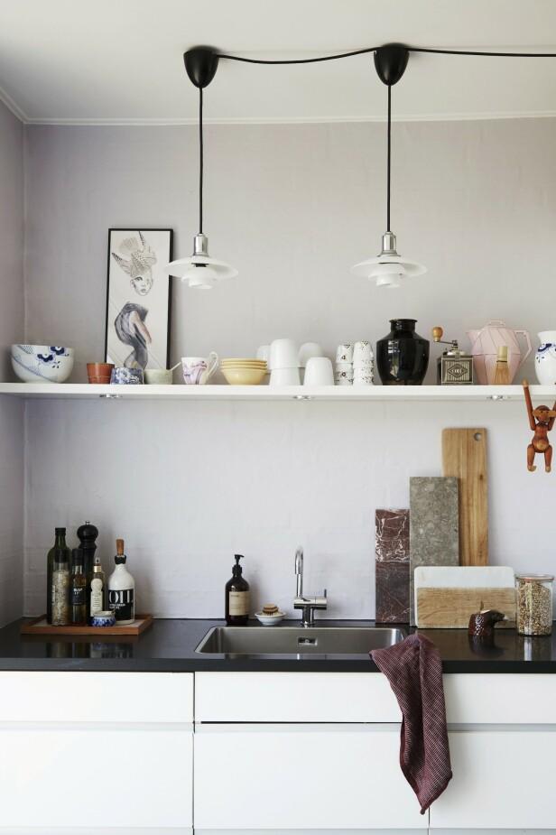 Pendlene er fra Louis   Poulsen, og serviset er fra Royal Copenhagen og loppemarkeder. Skjærebrettene og flisene er kjøpt i Italia. Veggen er malt i fargen «Lavendel Touch» fra Flügger. Selve kjøkkenet er fra HTH. Tips! Uten overskap blir kjøkkenet åpent og luftig. FOTO: Anitta Behrendt