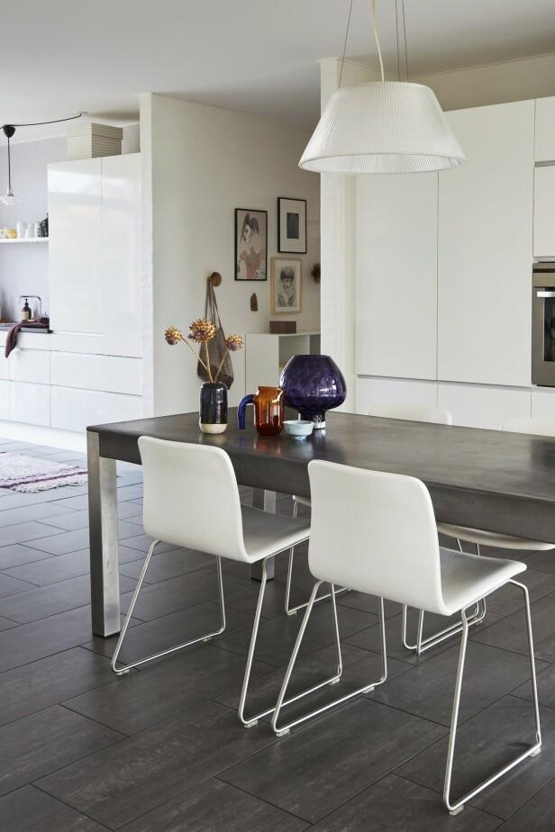 Det tunge spisestuebordet er fra Morten Voss, og rundt står hvite stoler fra Hay. Samlingen av glass og keramikk gir farge til rommet. Taklampen er fra Artemide. FOTO: Anitta Behrendt