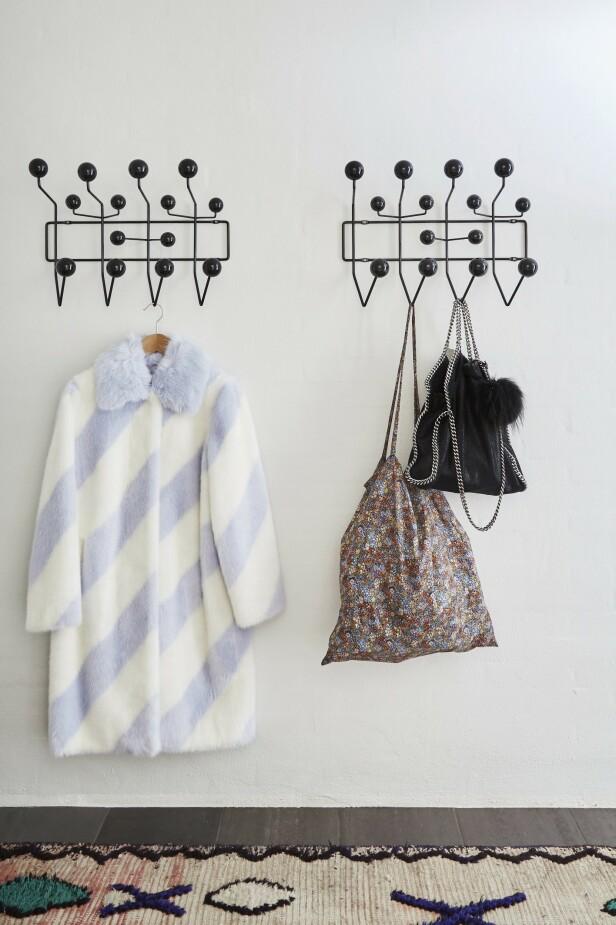 De grafiske, svarte knaggene fra Eames gir masse plass til jakker. Gulvteppet fra Hay med fine farger myker opp gangen. FOTO: Anitta Behrendt