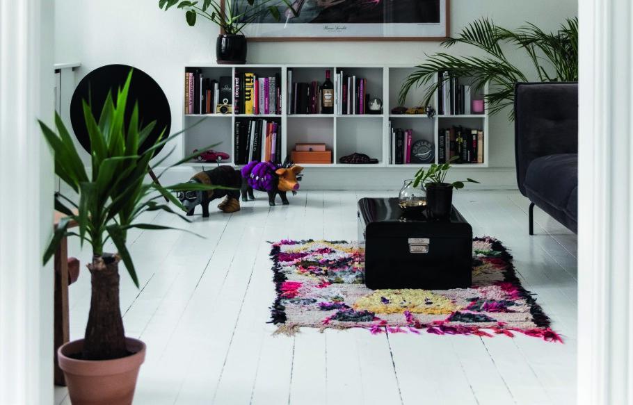 Plakaten, teppet og de mange bøkene i bokhylla «bråker» fargemessig, mens de hvite gulvene, veggene og hyllene får rommet likevel til å virke rolig. FOTO: Benjamin Lee Rønning Lassen