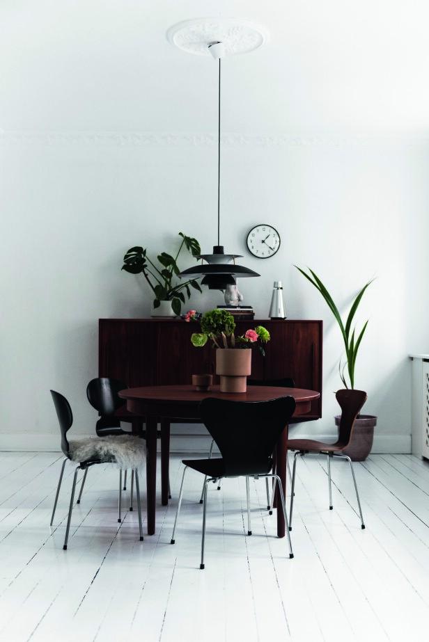 Camilla Rigmor har både stolene «Mauren», «Syveren» og «Myggen» rundt bordet, alle skapt av Arne Jacobsen. På bordet står Oyoys nytolkning av terrakottakrukken med noen grønne og rødlige blomster satt tilfeldig oppi. Den klassiske PHlampen er fra Louis Poulsen. Tips! Miks ulike stoler rundt spisebordet. Det skaper et lekent og av avslappet uttrykk. FOTO: Benjamin Lee Rønning Lassen