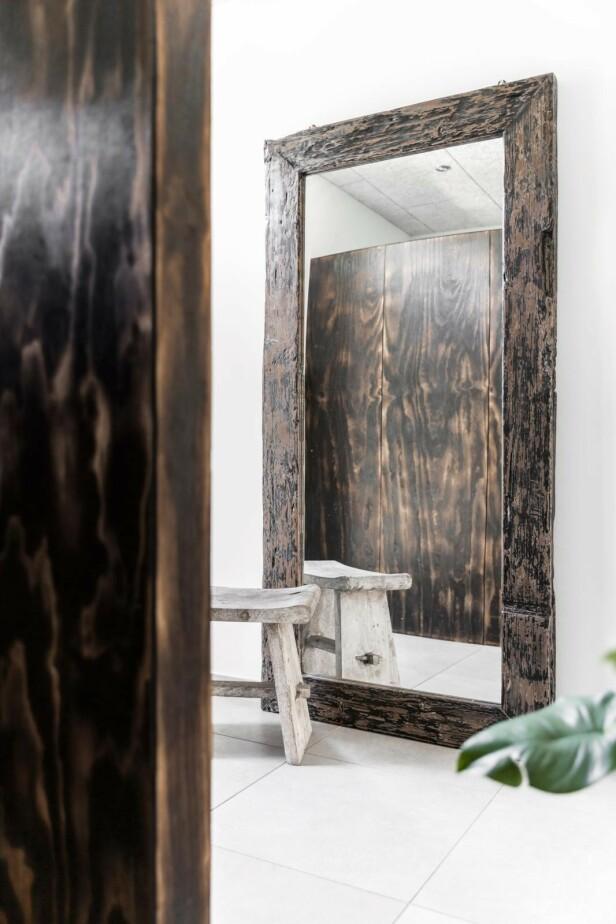 I gangen står et stort speil med en rustikk treramme. Diana elsker å innrede med materialer som tilfører varme og sjarm. FOTO: Another Studio