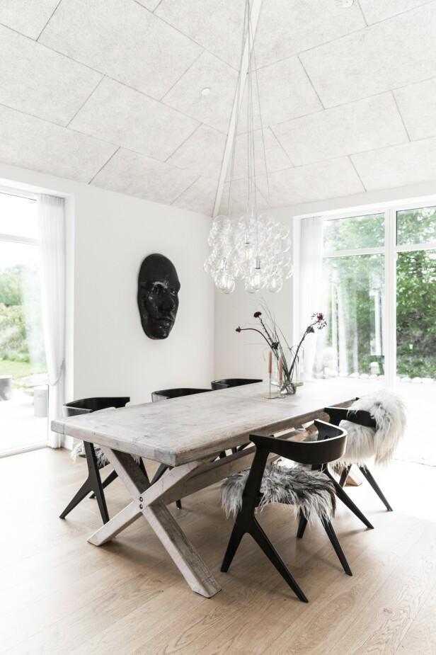 Bordplaten på det store spisebordet er egentlig en gammel dør fra Kina. Over bordet henger hele sju taklamper som Diana har hengt sammen så de oppleves som én stor lampe. FOTO: Another Studio