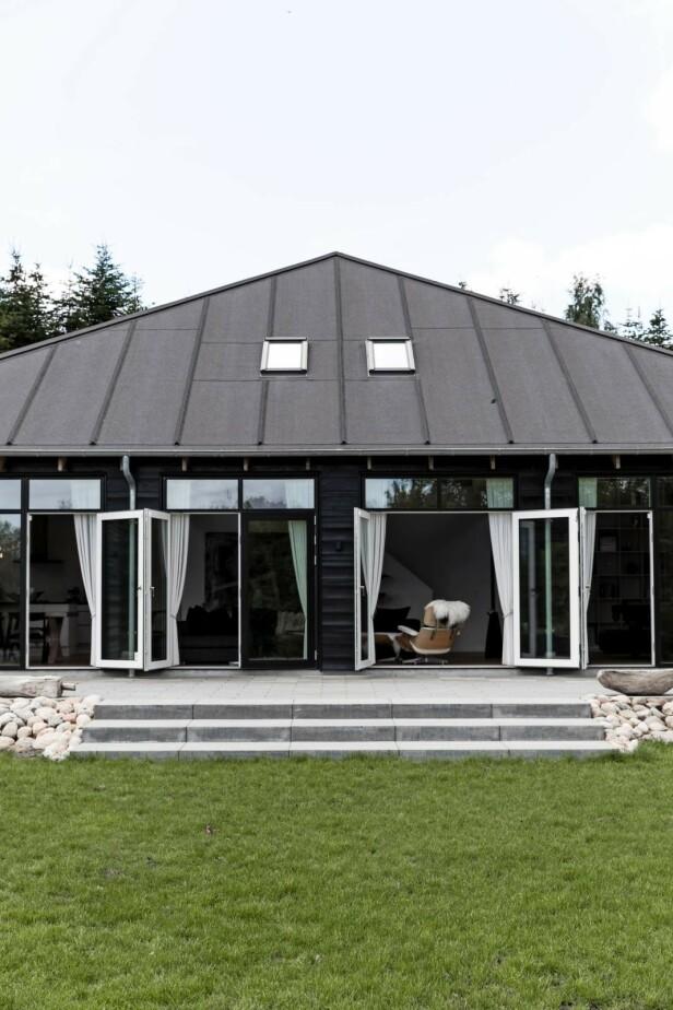 Dee store glassdørene kan åpnes sånn at stuen og uteområdet henger sammen. FOTO: Another Studio