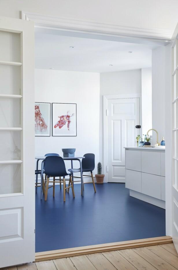Det blå linoleumsgulvet fanger oppmerksomheten og skaper kontrast til det hvite kjøkkenet. Paret satte franske dører i veggen mellom kjøkken og stue, så de kan stenge av for matos, men likevel føle seg som en del av selskapet. FOTO: Stylesystemet
