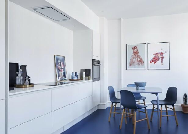 Gulvet på kjøkkenet er fra Forbo, kjøkkenet fra HTH og bord og stoler fra Normann Copenhagen. Den blå skålen er fra Beau Marché, og bildene er laget av Lasse Bekker Weinreich. Tips! Har du lyst på et gulv eller en vegg i en vågal farge, få med deg en prøve fra butikken hjem slik at du kan danne deg et inntrykk før du går «all in». FOTO: Stylesystemet