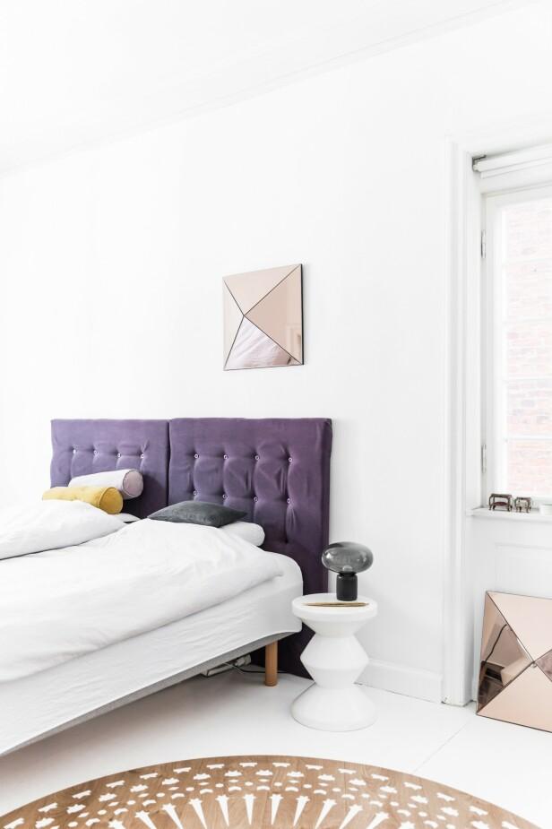 Hele soverommet er hvitt, fra gulv til tak. For å sprite opp, har Mai-Britt laget en senge gavl i lilla og pyntet opp med speilkunst fra merket Reflections. FOTO: Julie Wittrup og Mikkel Dahlstrøm/Another Studio
