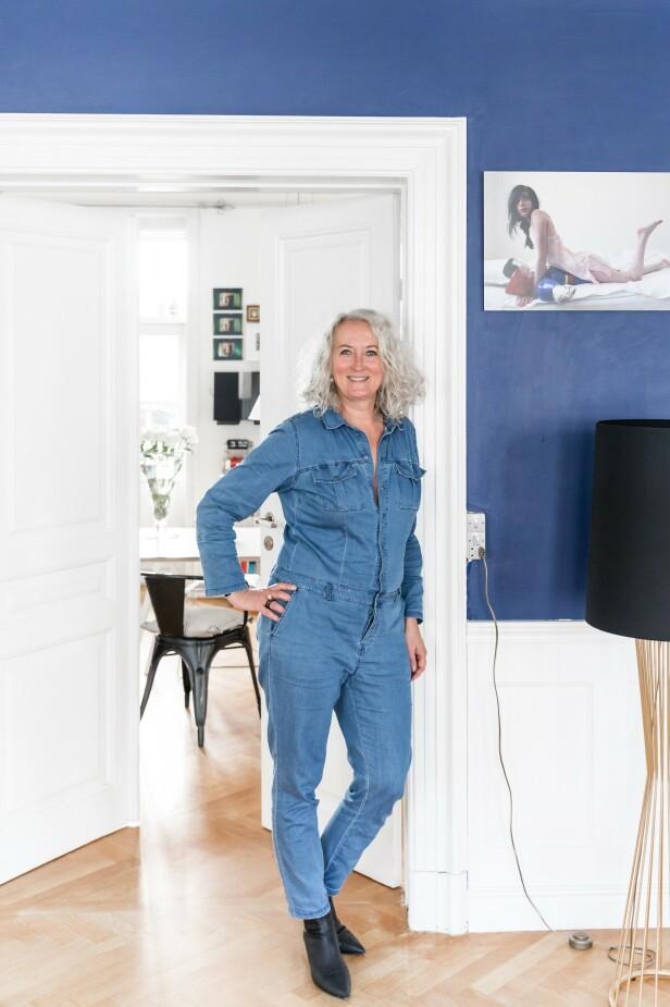 Her står Mai-Britt i dør åpningen mellom stue og kjøkken. Ved siden av henne står messinglampen Tulip designet av Autoban. FOTO: Julie Wittrup og Mikkel Dahlstrøm/Another Studio