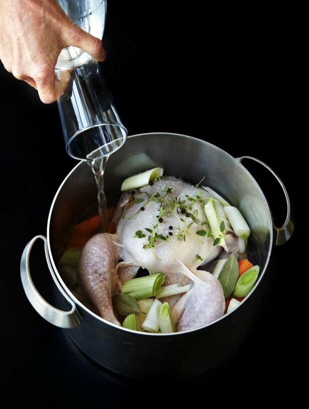 1. Legg kyllingen i en stor gryte. Skrell gulrot og persille rot, og skjær dem i grove biter. Rens purren, og skjær den i grove biter. Legg alle grønnsakene i gryten sammen med laurbærblader, timian- kvister, salt og pepperkorn. Dekk kyllingen med vann, og bring det i kok. La kyllingen småputre på svak varme i 45 minutter til den er mør. FOTO: Betina Hastoft
